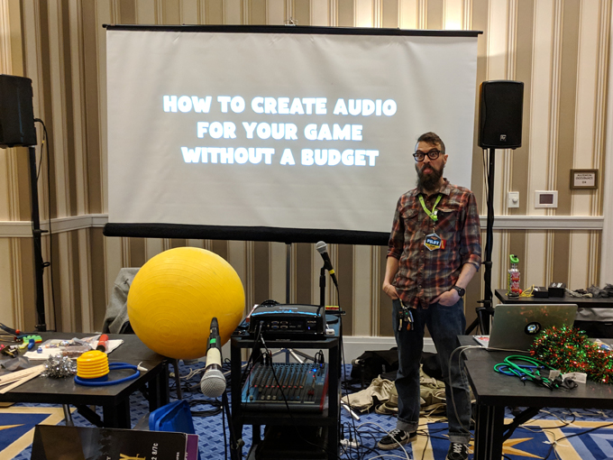 Ocean stands in front of his panel title How to Create Audio for your game on a Budget sticking his tongue out at you.