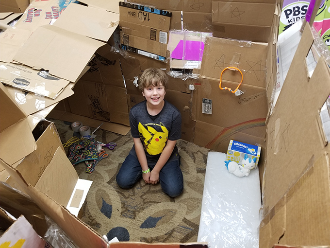 Little girl sitting in a cardboard fort smiling out at you.