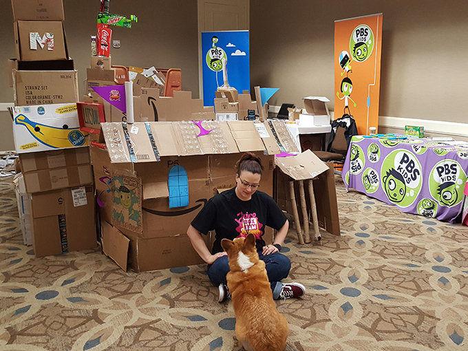 Woman sitting in front of a card board fort. Smiling down at a corgi looking up at her.
