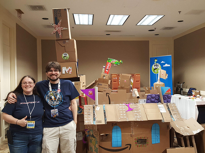 A lady and a man stands in front of a large card board fort.