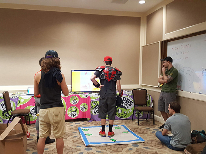 DJ Cutman stands on a makeshift game with a group watching him play.