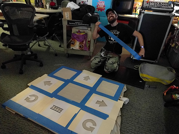 A man gets ready to put tape on a large game board.