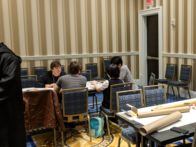 A group of developers work on a paper prototype game at one of our game jams.