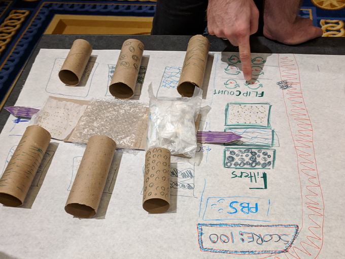 A water filtration video game paper prototype made from cardboard, plastic materials, pens and tape.